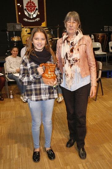 Graci Arias entregando una de las jarras a una de las alumnas